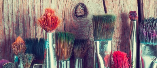 row of artist paintbrushes closeup on old wooden rustic table retro stylized